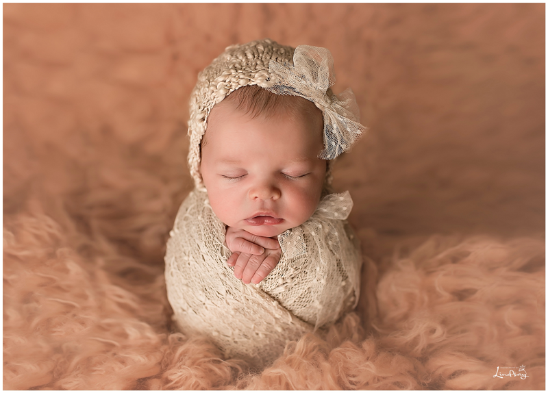 Baby Asleep And Wred In Cream Knit Wrap On Peach Flokati Rug Older Siblings Holding Newborn Sister Photography By Lindsay