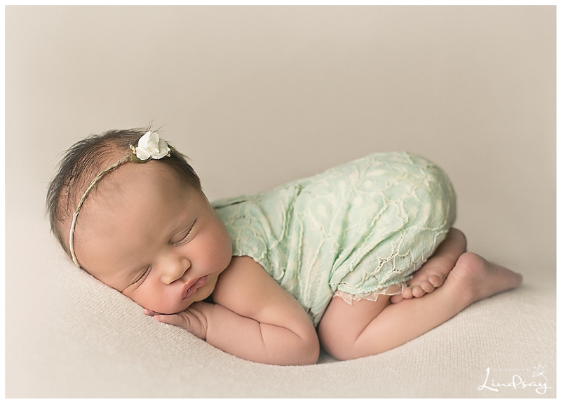 Newborn baby girl asleep on cream blanket with light green romper on