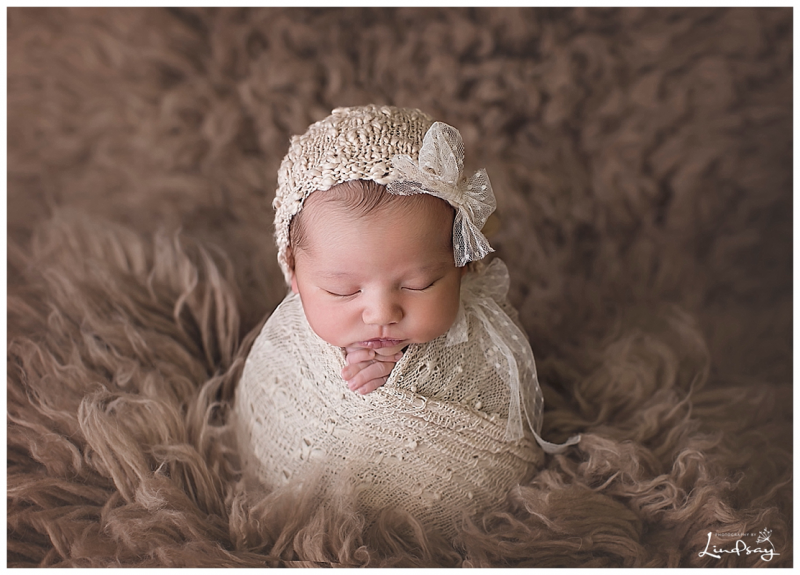 Newborn girl swaddled in cream wrap on a brown flokati rug while at Photography by Lindsay Martinsburg studio.