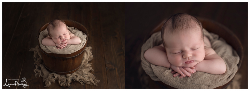 Baby boy asleep in wooden bucket at photography by Lindsay studio.
