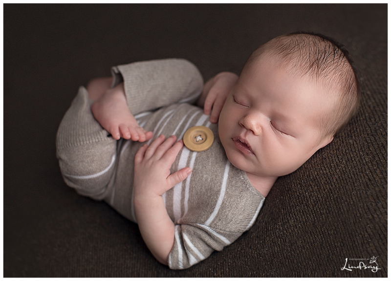 Baby boy asleep on back wearing brown romper on a brown blanket at martinsburg studio.