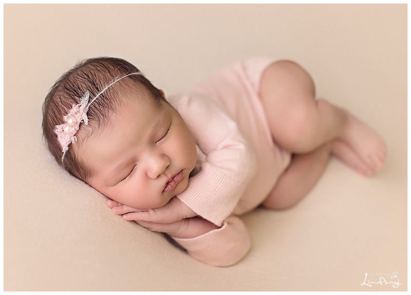 newborn baby girl asleep on cream blanket at photography by Lindsay stuido.