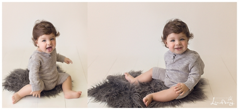 12 month old baby boy in grey romper smiling at Photography by Lindsay studio.