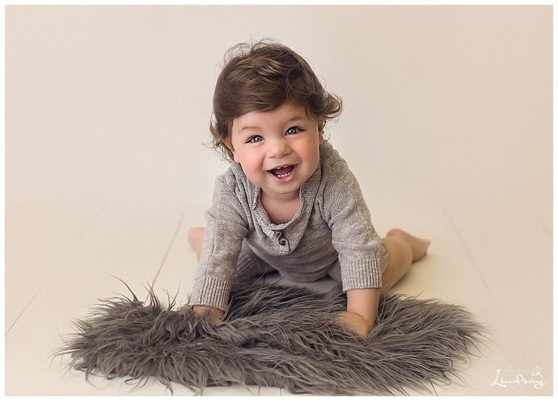 Baby boy wearing grey romper on his knees with big smile while at Photography by Lindsay studio.