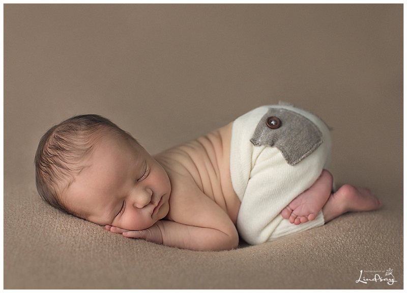 Newborn baby boy asleep on brown blanket with cream pants at Photography by Lindsay studio.