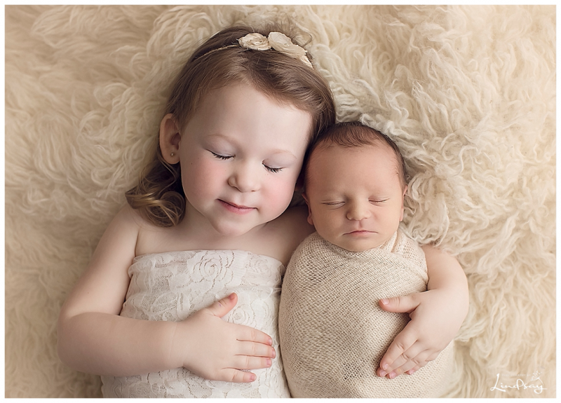 Big sister snuggling with newborn brother at Photography by Lindsay Martinsburg studio.