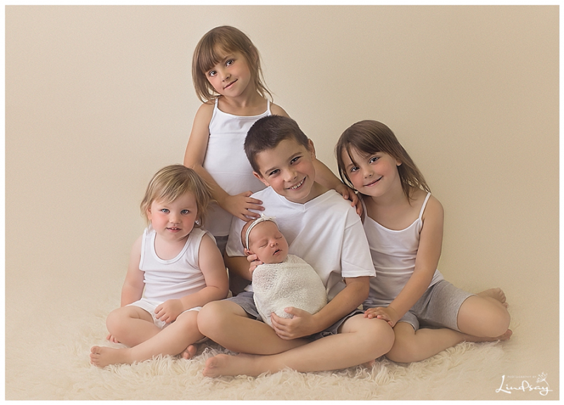 4 older siblings with newborn sister on cream rug at Photography by Lindsay studio.
