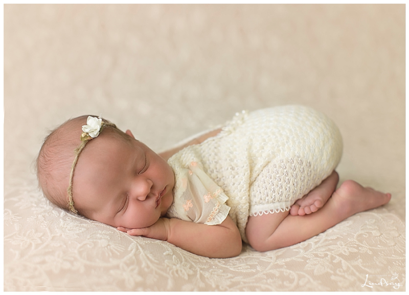 Baby girl asleep on lace fabric while wearing cream romper at Photography by Lindsay studio.
