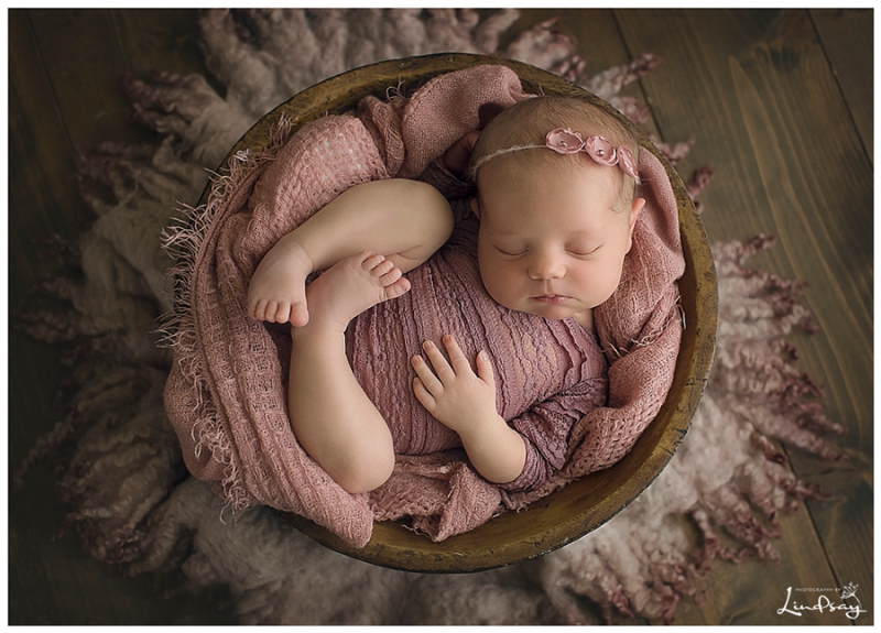 Baby girl wearing lace mauve outfit and sleeping in wooden bowl at Photography by Lindsay studio.