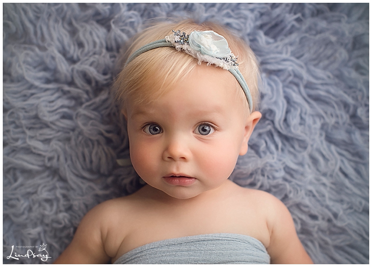 Baby girl looking at the camera while laying on blue rug at Photography by Lindsay Martinsburg studio.