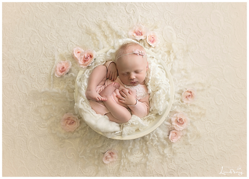Baby girl in pink romper while asleep in cream wooden bowl on a cream lace backdrop.