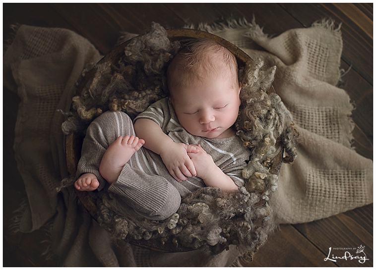 Baby boy in brown romper asleep in wooden bowl while at Photography by Lindsay studio.