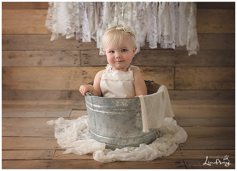 Baby girl in bucket with lace romper and smiling at the camera at Photography by Lindsay Martinsburg studio.