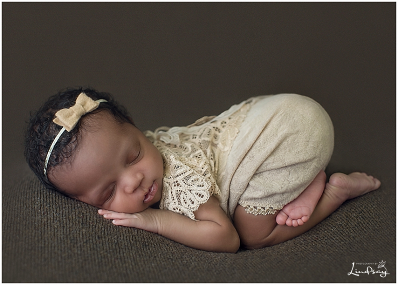 Baby girl wearing brown lace romper while asleep on brown blanket at Photography by Lindsay studio.