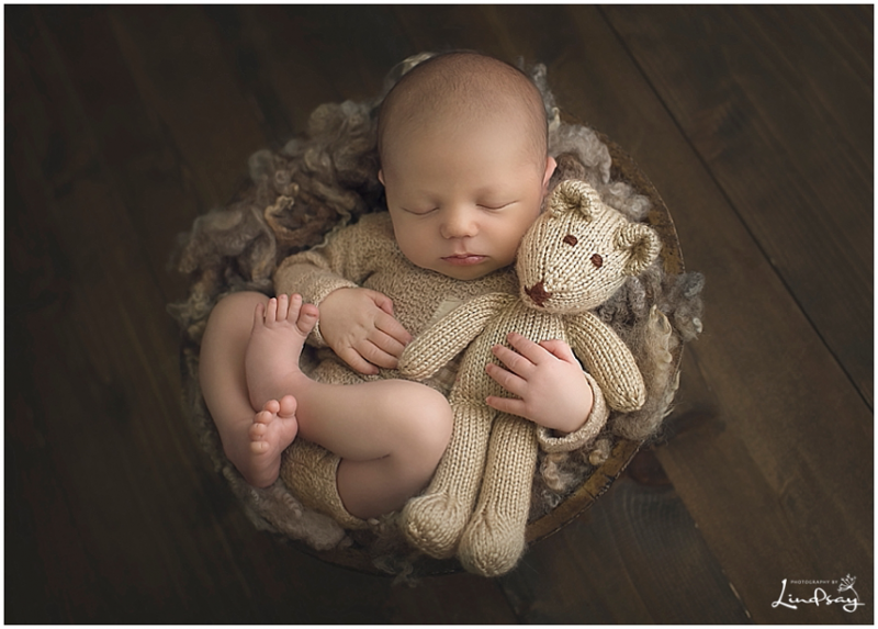 Baby boy asleep in wooden bowl and holding a knit teddy bear while at Photography by Lindsay studio.
