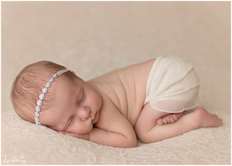 Newborn girl asleep on her tummy on a lace blanket while at photography by Lindsay studio.