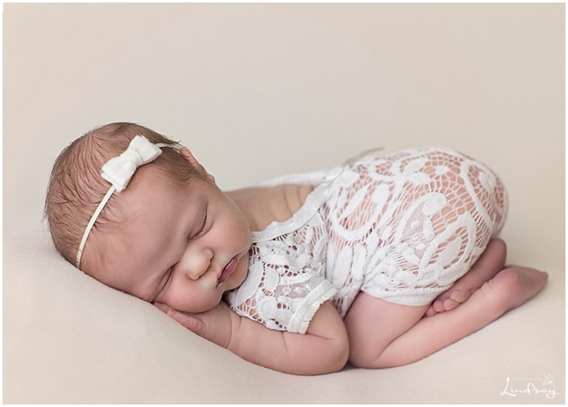Newborn girl asleep on cream blanket in whit lace outfit while at Photography by Lindsay studio.