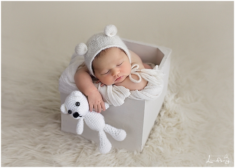 Baby girl asleep in wooden box while holding stuffed bear and wearing bear hat at Photography by Lindsay studio.