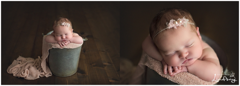 Newborn girl asleep in bucket with light pink wrap at Photography by Lindsay studio.
