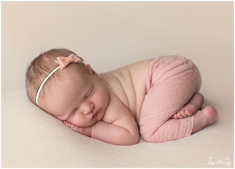 Photo of newborn girl wearing lace pants and asleep on tummy by Lindsay Barnhart baby photographer leesburg virginia.