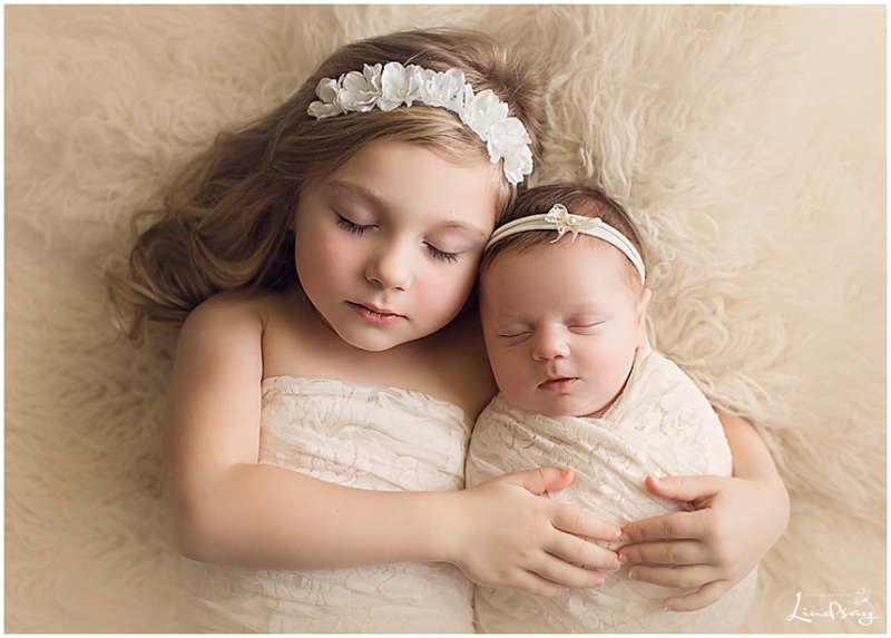 Sibling image of baby girl with big sister alseep on cream rug at Photography by Lindsay studio.