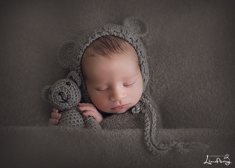 Baby boy wearing grey bear hat and holding stuffed grey bear on a grey blanket at Photography by Lindsay studio.