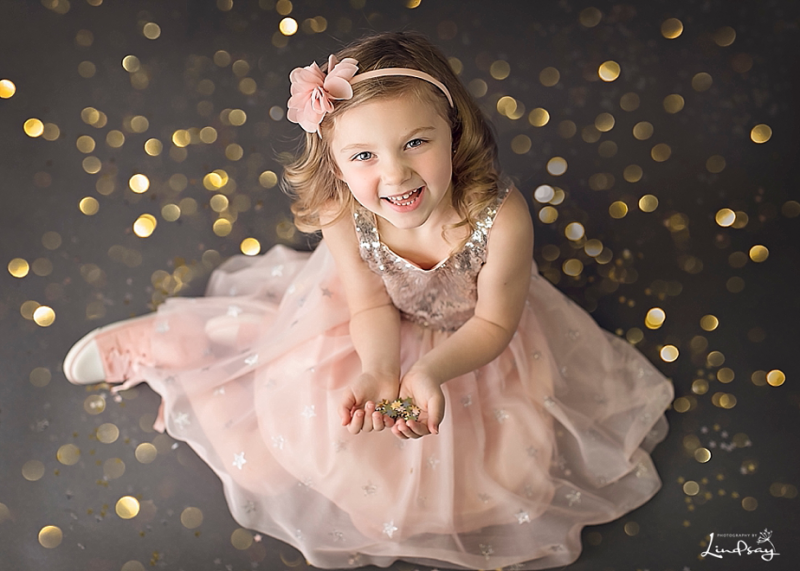 Image of little girl in pink dress with gold glitter everywhere while at Photography by Lindsay studio.