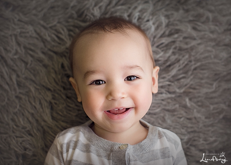 Close up of baby boy laying on his back on a grey rug and smiling at the camera.