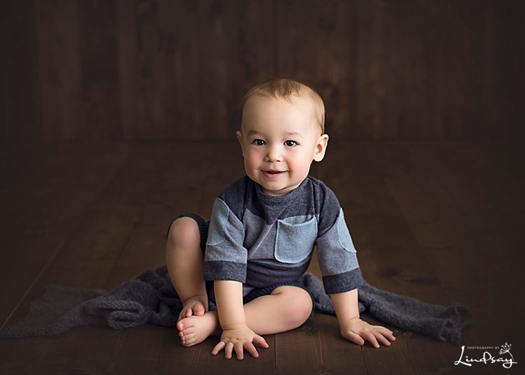 One year old wearing stripped blue romper and sitting on dark wood backdrop at Photography by Lindsay studio.