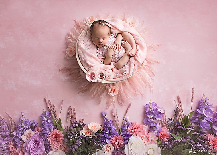Baby girl alseep in bowl with flowers below at Photography by Lindsay Martinsburg WV studio.