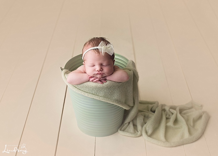 Baby girl in bucket and asleep while at Photography by Lindsay studio.