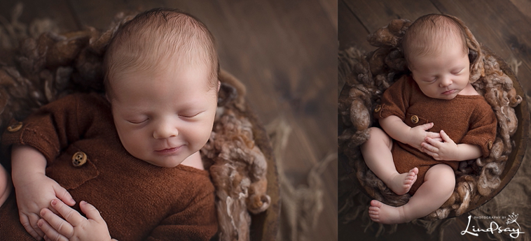 Newborn baby boy photos of baby wearing rust colored romper and asleep in a wooden bowl.