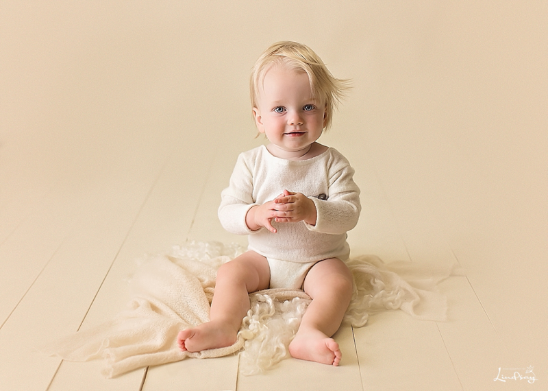 Baby boy sitting on cream floor wearing cream romper at Photography by Lindsay studio.