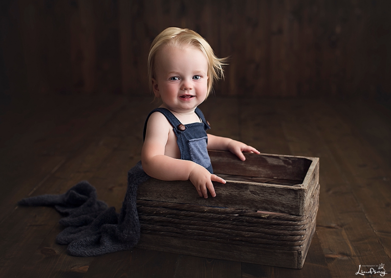 12 month old boy sitting in wooden box and wearing blue overalls while smiling at camera.