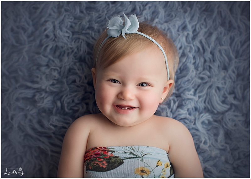 Baby girl wrapped in blue floral wrap and smiling while laying on blue blanket at Photography by Lindsay studio.