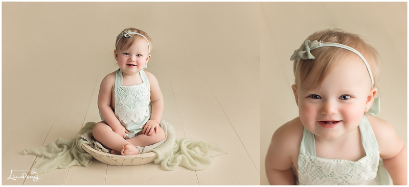 10 month old girl wearing green romper and sitting on cream wooden floor and smiling.