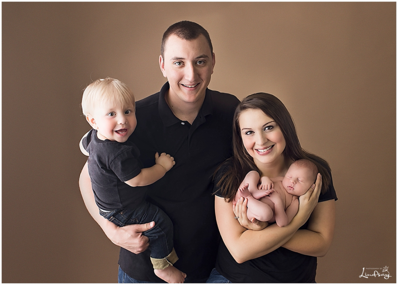 Family with newborn baby and big brother at Photography by Lindsay studio.