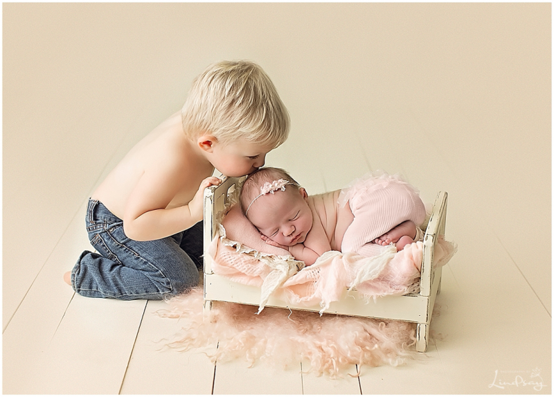 Big brother kissing his baby sister on head while she sleeps in wooden bed at Photography by Lindsay studio.