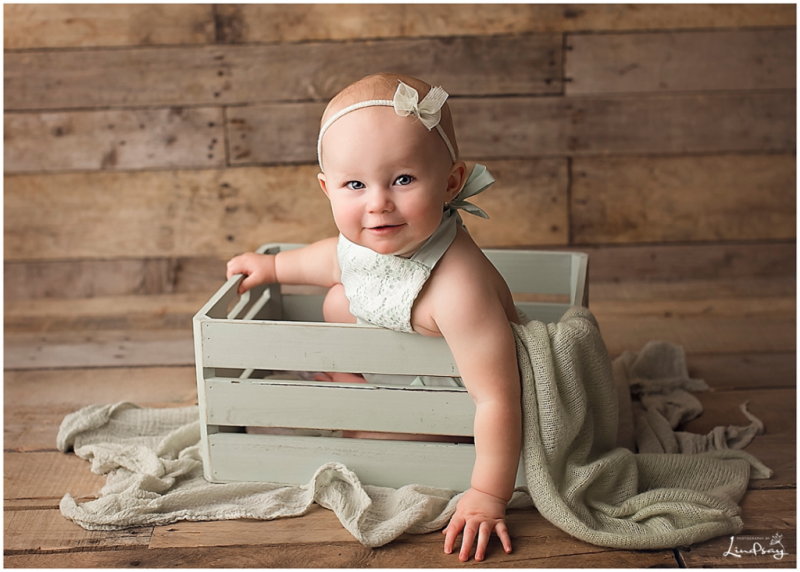 One year old in green box with green romper smiling at the camera while at Photography by Lindsay studio.