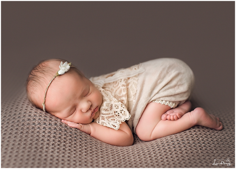 Newborn girl asleep on brown blanket while wearing brown lace outfit at Photography by Lindsay studio.