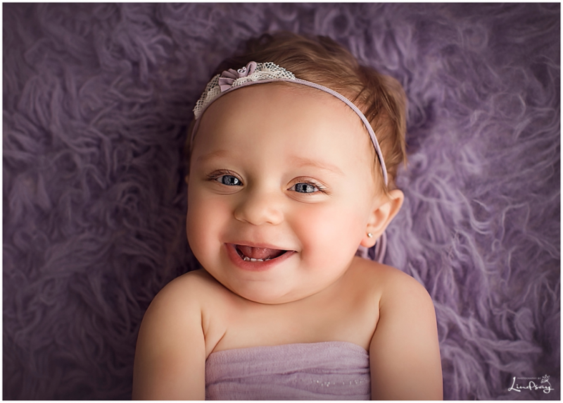 12 month old laying on purple rug and smiling while at Photography by Lindsay studio.