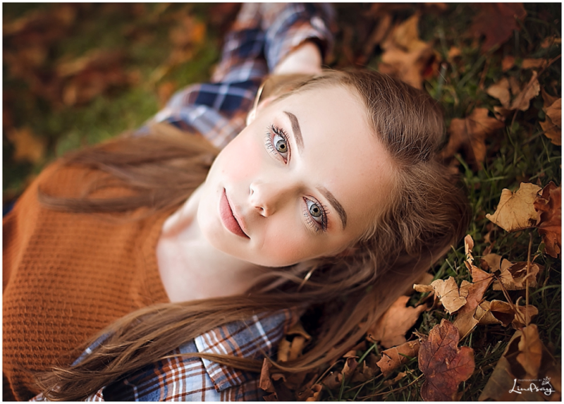 senior portraits of teen laying down on her back and looking up at the camera with fall leaves around her.