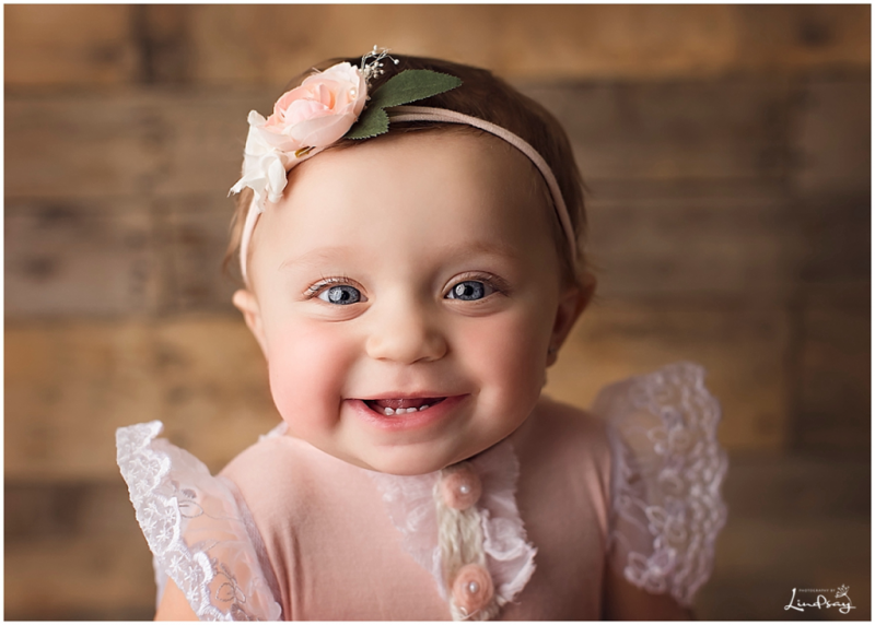 Close up of one year old girl smiling at camera while wearing pink and white lace outfit.