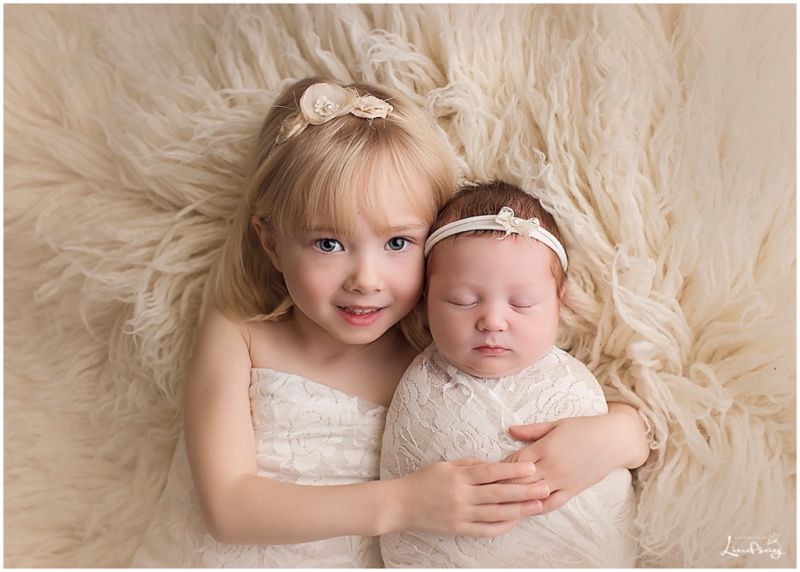 Baby girl swaddled in cream lace wrap and laying with her big sister on cream flokati rug.