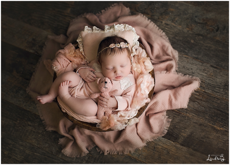 Baby girl asleep in wooden bowl while holding pink stuffed bear and wearing pink romper.
