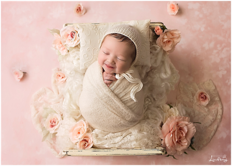 Newborn swaddled on cream bed with pink flowers taken by local baby photographer, Photography by Lindsay.