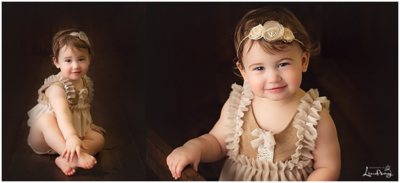 Two images of one year old sitting on dark wood set up and wearing brown romper while at Photography by Lindsay studio.