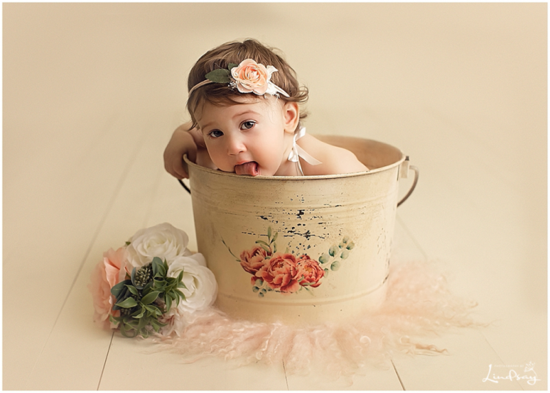 1 year old sitting in cream bucket and licking the bucket while at Photography by Lindsay studio.