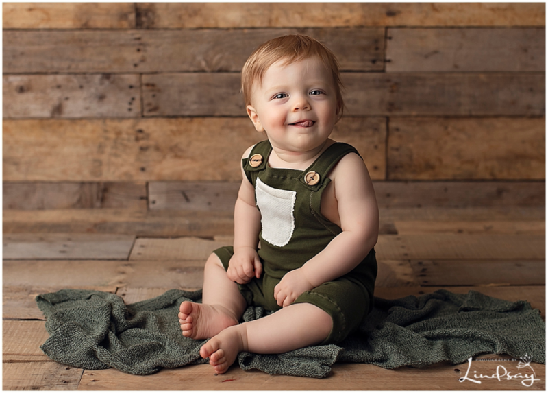 Baby boy wearing green overalls and sitting on wooden backdrop while at Photography by Lindsay Martinsburg studio.