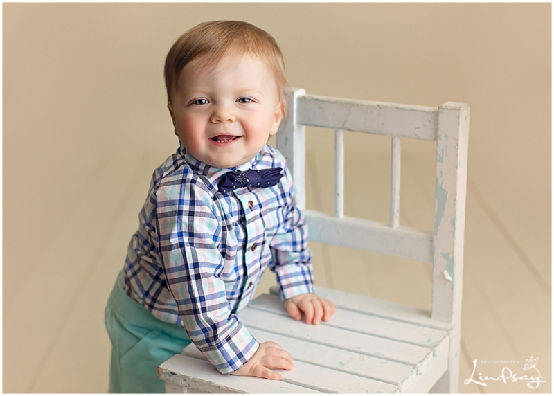 12 month old boy wearing bowtie and standing up against a wooden chair while at Photography by Lindsay studio.